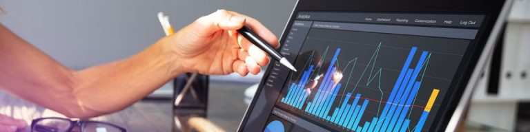 Woman gesturing with pencil towards graph on laptop