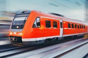 Bright orange passenger train in motion.