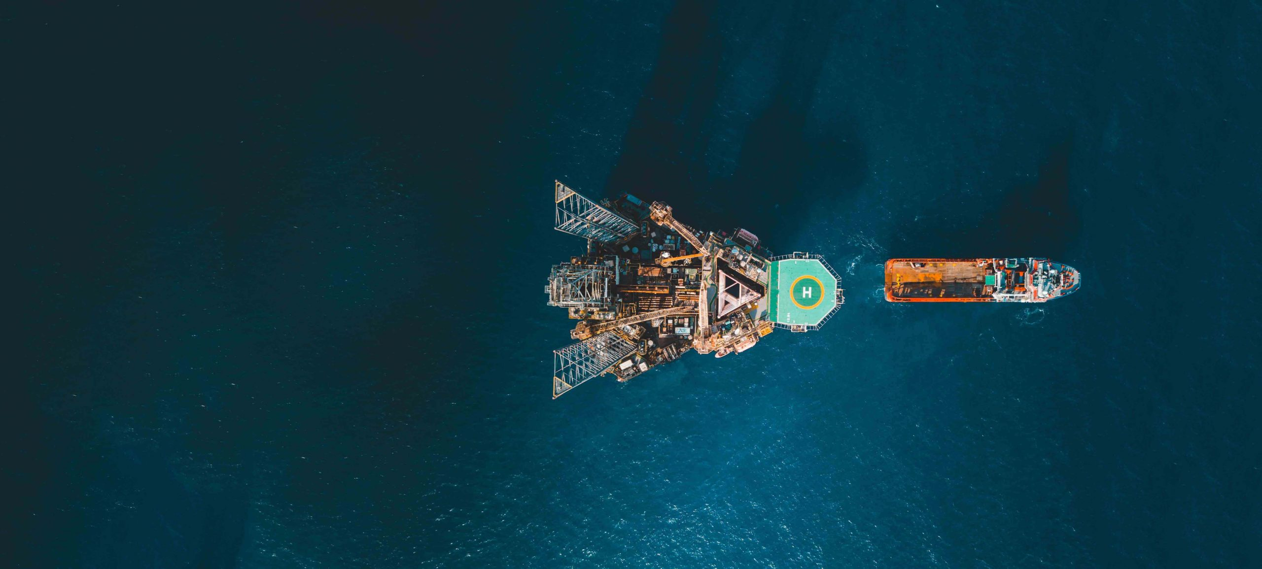 Bird's eye view of oil rig and orange boat in ocean
